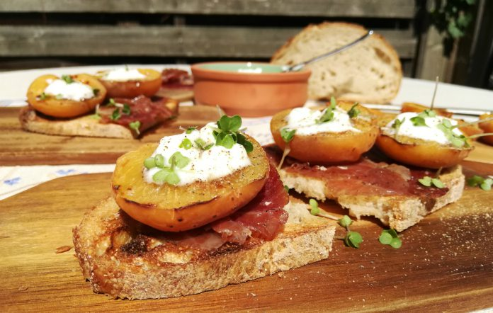 2 tapas with Iberico ham, roasted apricots and cottage cheese on a toast, served outdoors in a garden